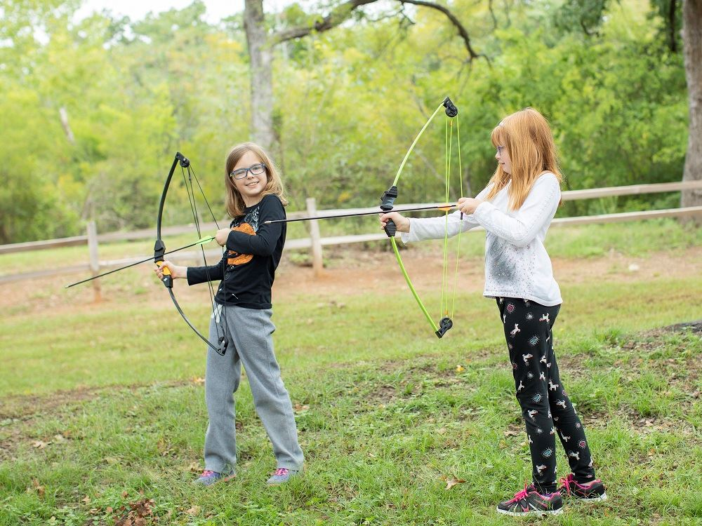 Two girls shooting a bow and arrow