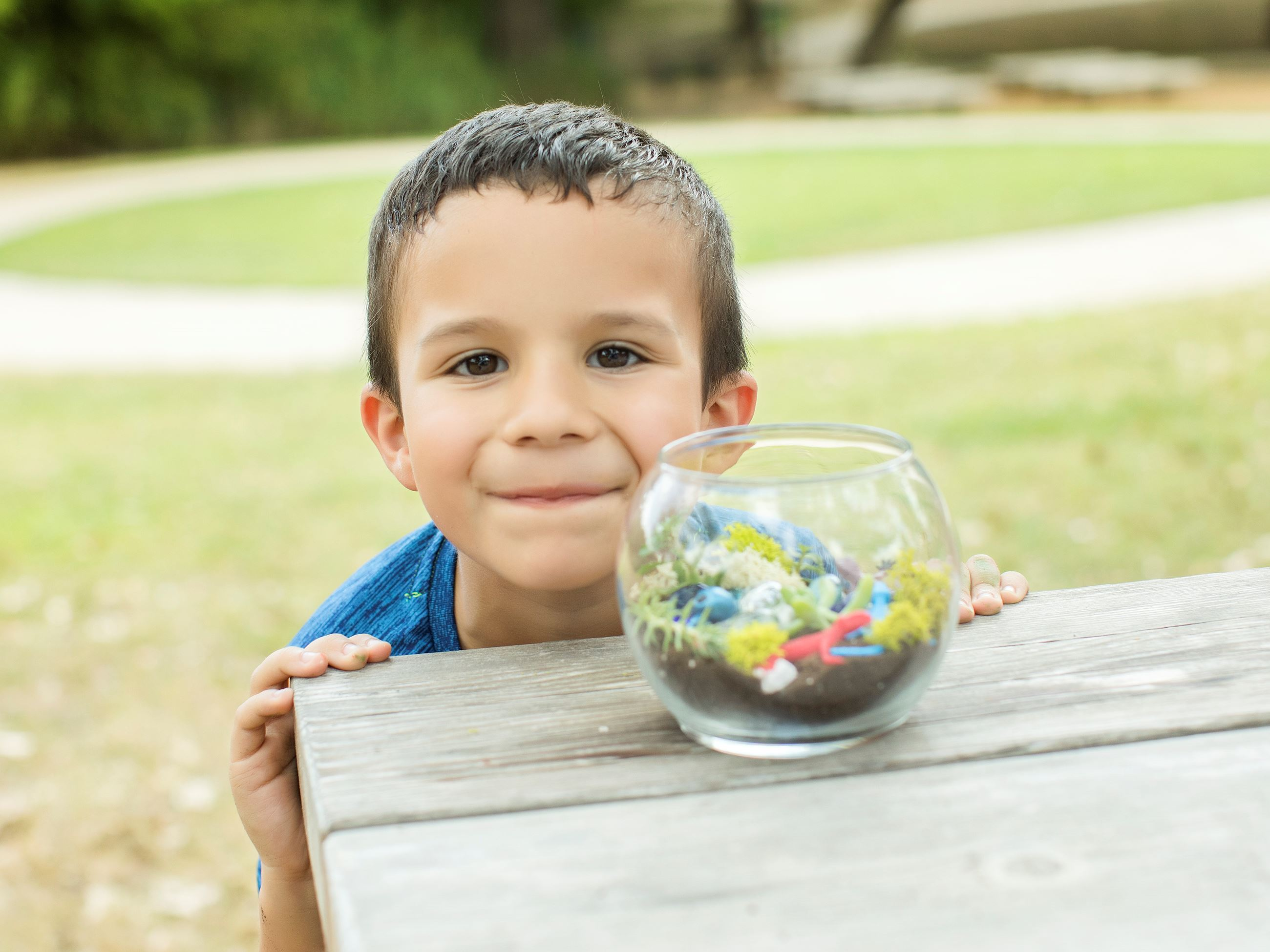 Boy looking with glass bowl filled with dirt and dinosaur figures