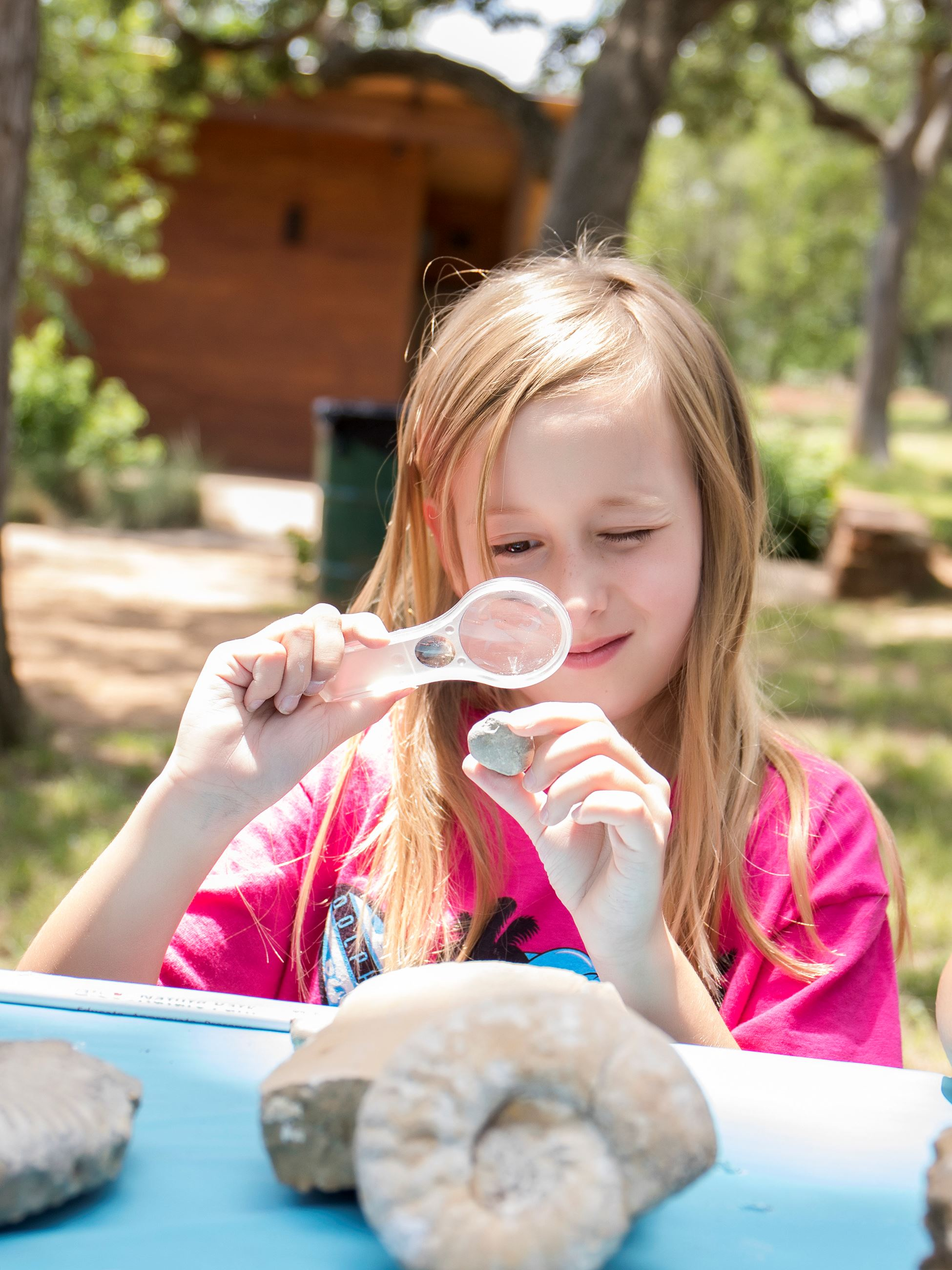 Girl looking at fossil with magnifying glass