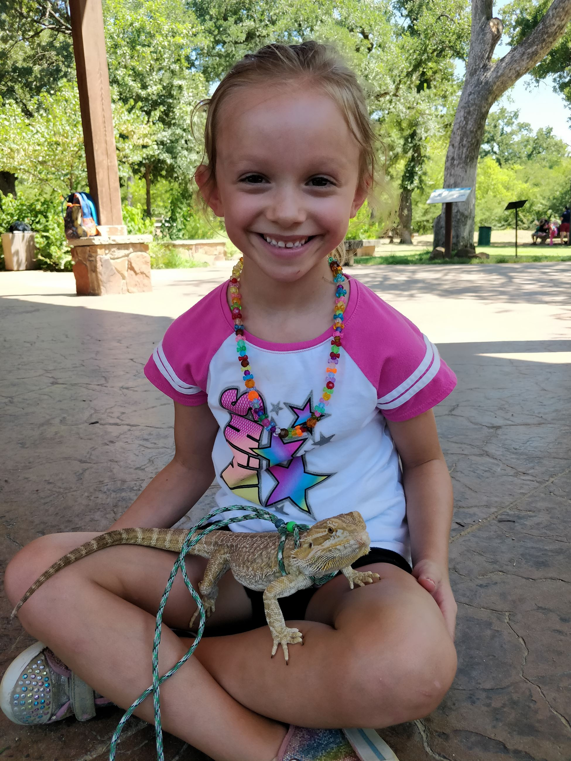 Girl smiling holding bearded dragon