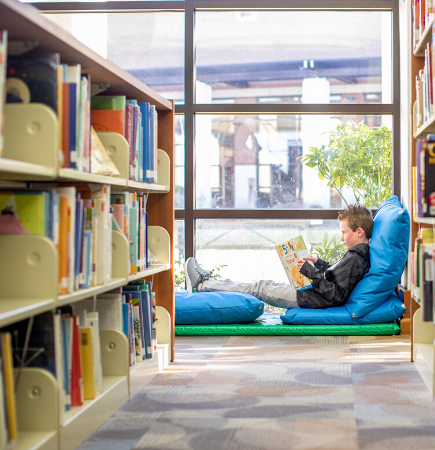 child reading in the library on blue pillows