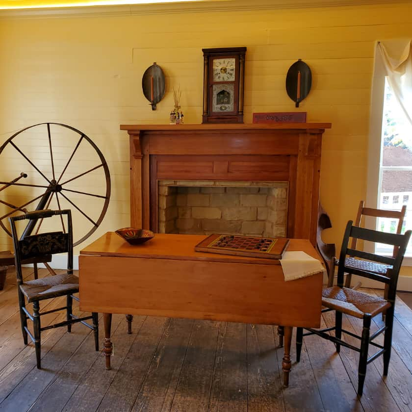 Table, spinning wheel and mantle in the log house room